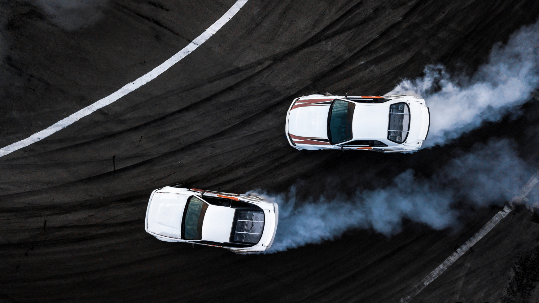 Two Racing Cars Drifting Around a Turn