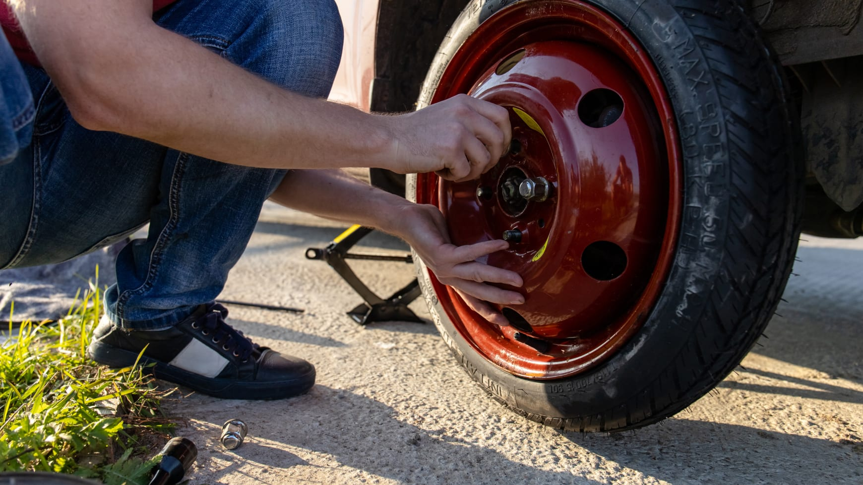 A Stranded Driver Putting on a Temp-Spare Tire