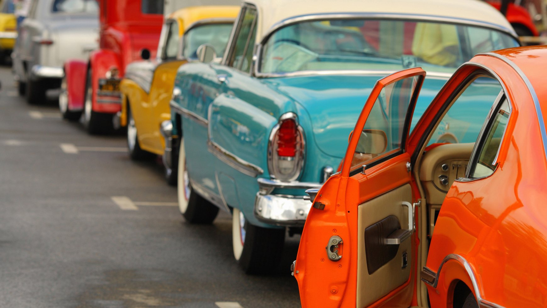 Several Antique Cars Lined Up on the Road