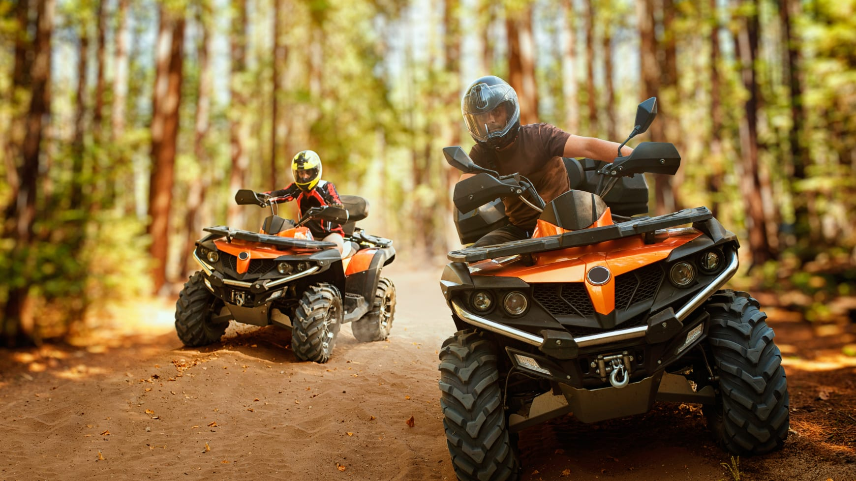 Two All Terrain Vehicles Driving Through the Woods