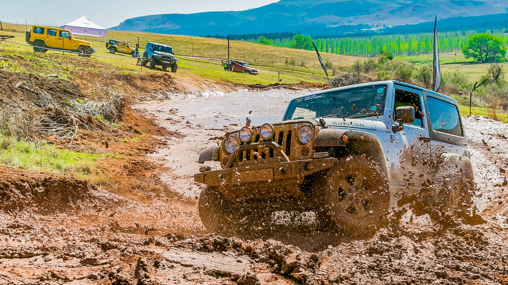 A Jeep Equipped with Mud Tires Splashing Through the Hillside