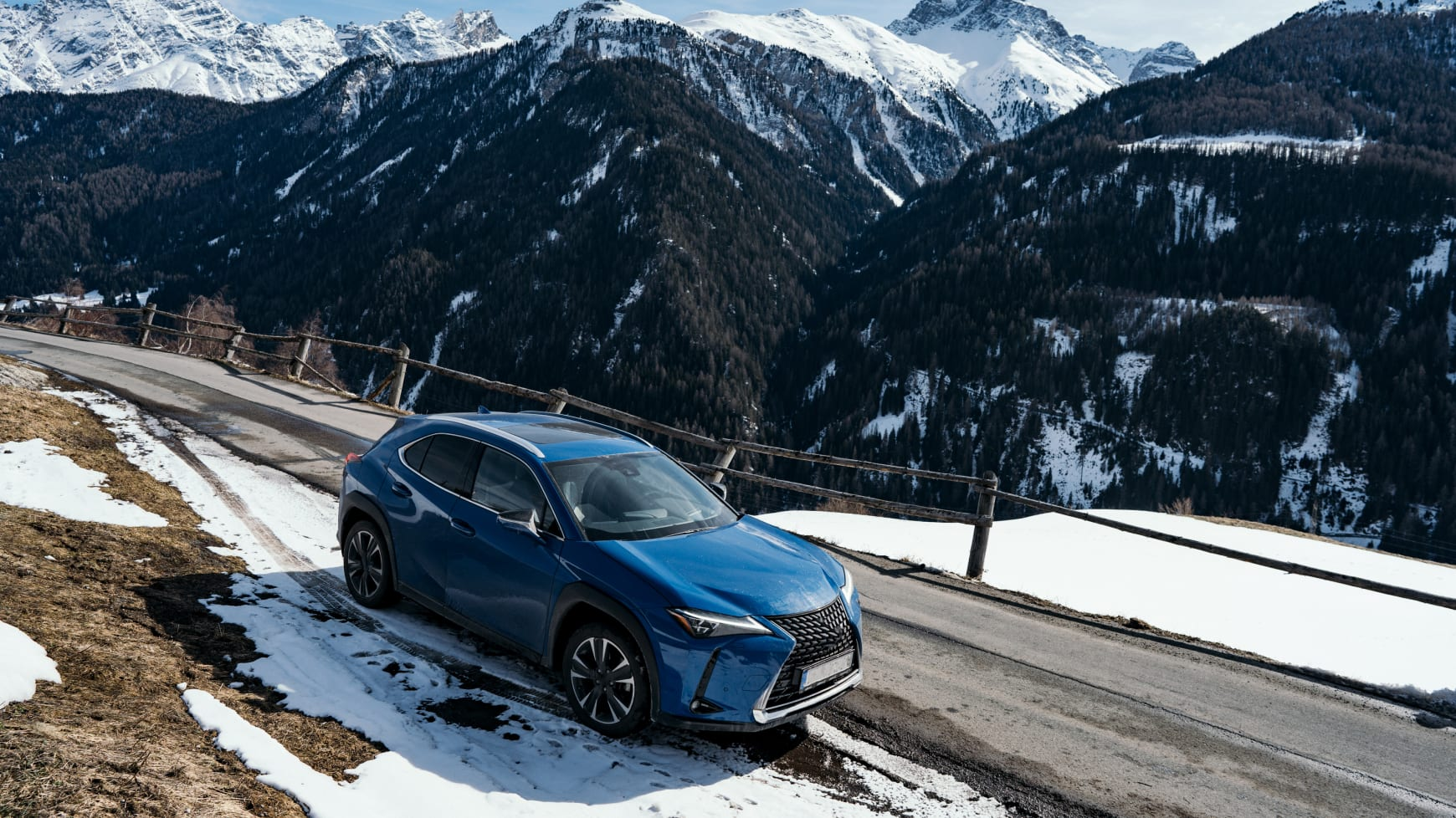 A Crossover Vehicle Driving Through Mixed Weather Conditions in the Mountains