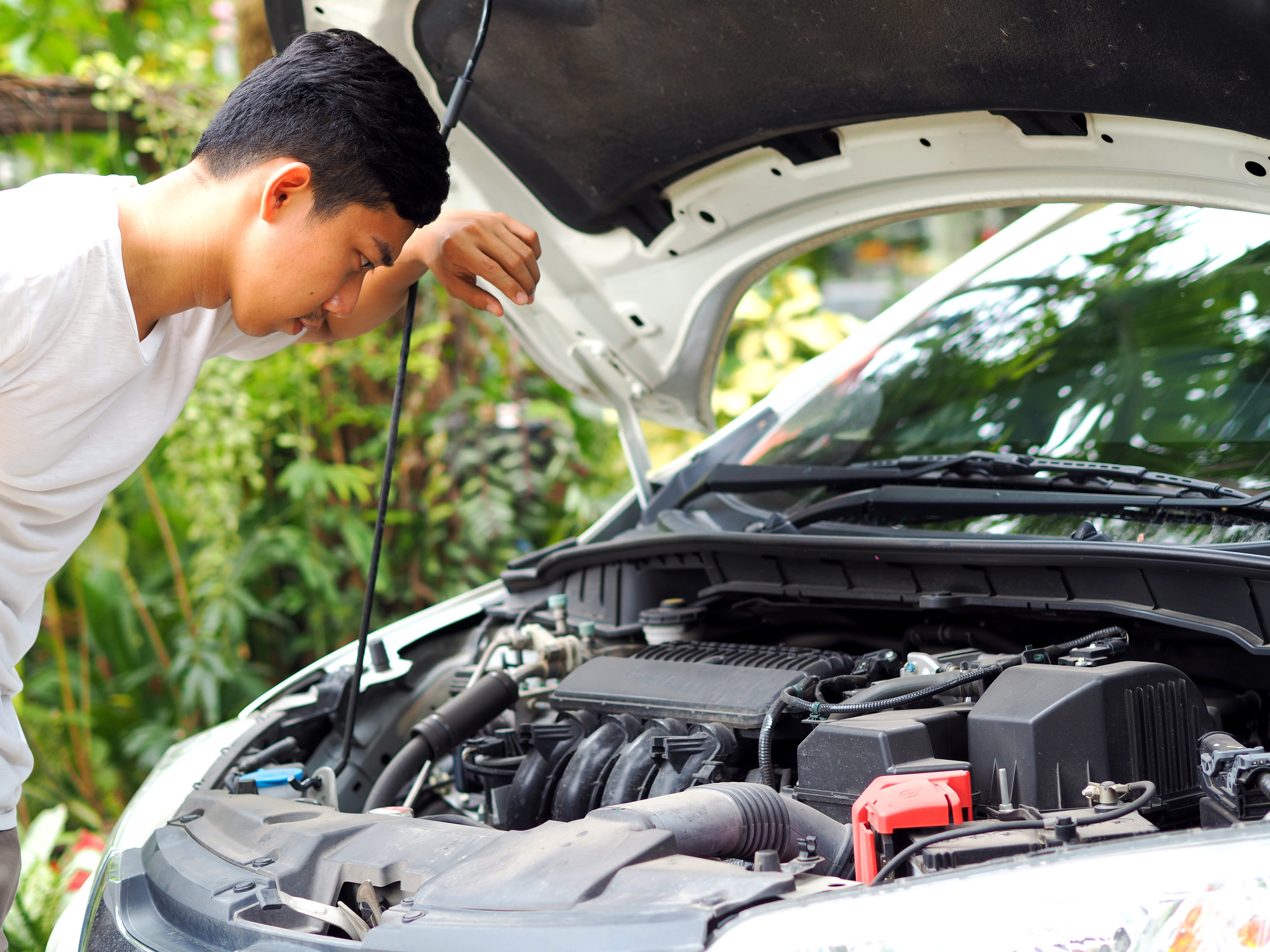 Man in White Tshirt Looking at Engine for Car Maintenance