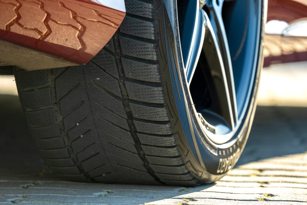 A closeup of a properly installed tire on a red car, showcasing its tread.