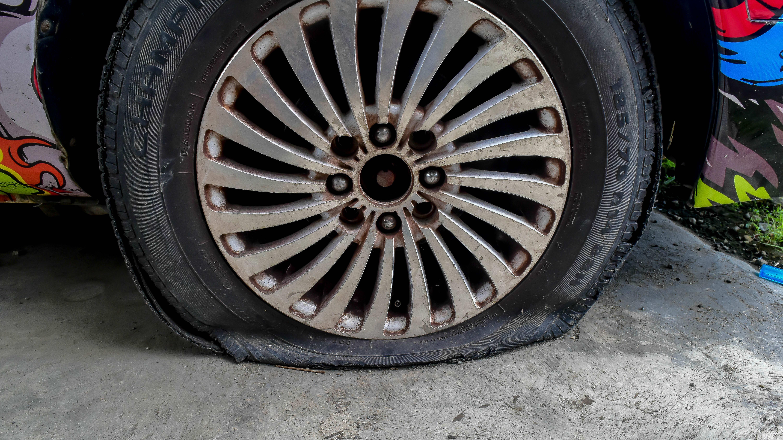 A flat tire on a passenger car with a unique paint job.