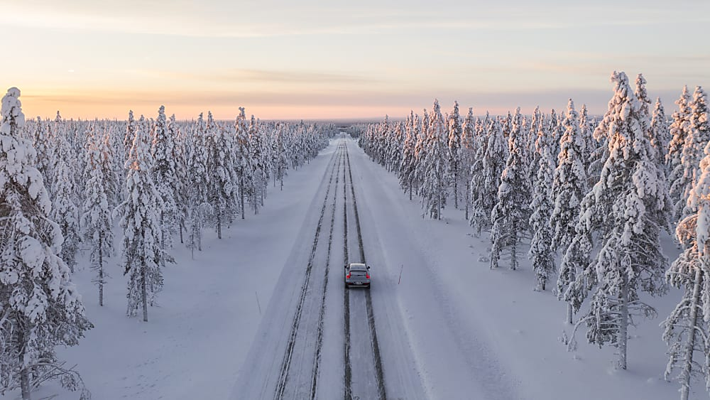 Nokian Hakkapeliitta 10 tires on a passenger car driving away on a snowy day.