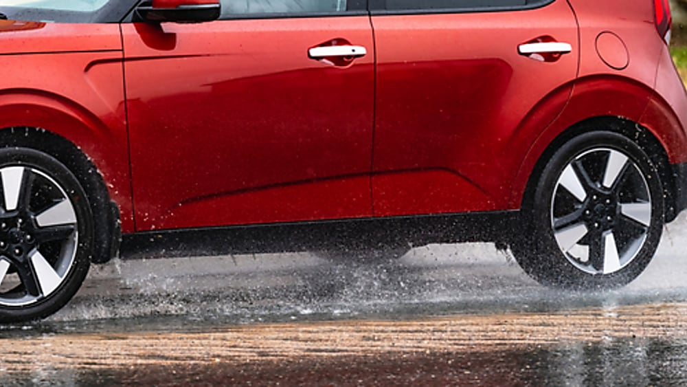 A red SUV driving on a wet road.